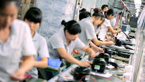 China - October 2013: Chinese female factory workers assembling manufactured parts, Mainland China, East Asia