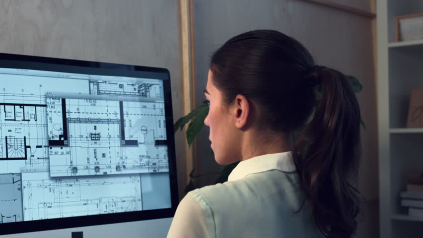 Woman working at home office architectural plans