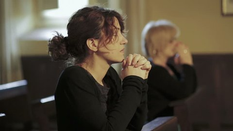 intense prayer of two women in a church: religion, faith, devotion, Catholics