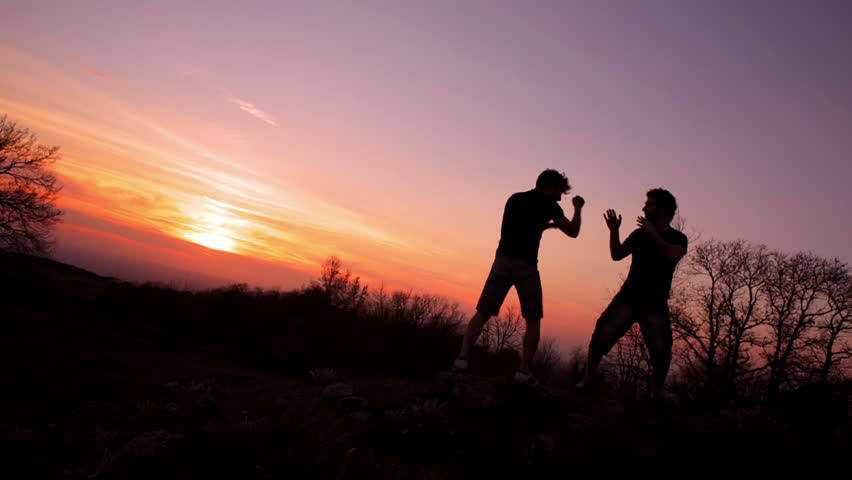 Silhouettes of two fighters on sunset fiery background: martial art, fight | Shutterstock HD Video #6709648