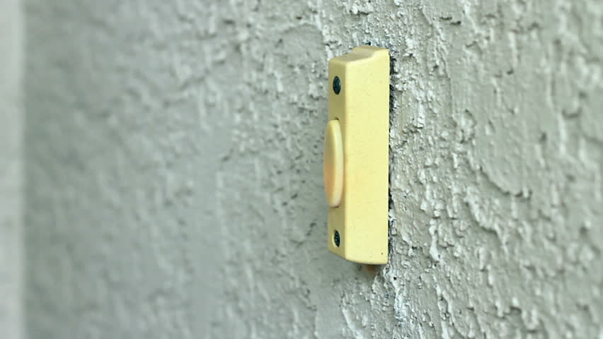 A close up of a male finger pressing a doorbell.
