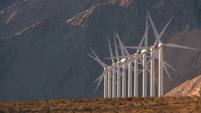 Rows of wind turbines producing clean alternative energy in barren landscape