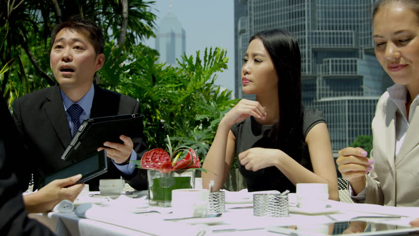 Ambitious Asian Chinese Caucasian corporate business colleagues discussing future plans using wireless tablets coffee outdoors city rooftop restaurant shot on RED EPIC | Shutterstock HD Video #6724969
