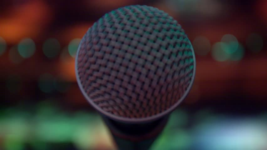 View of microphone on stage facing empty auditorium.  Colorful spotlights