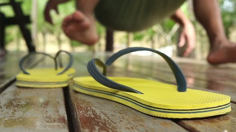 Flip flops or thongs in foreground as a very relaxed man swings on a hammock in the blurred background.
