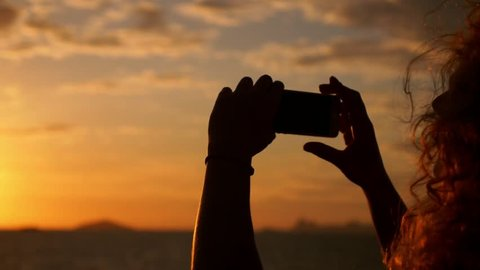 Young Woman with Curly Hair Taking Picture with Smartphone at Amazing Sunset in Sea Voyage on the Sailing Ship. Slow Motion.