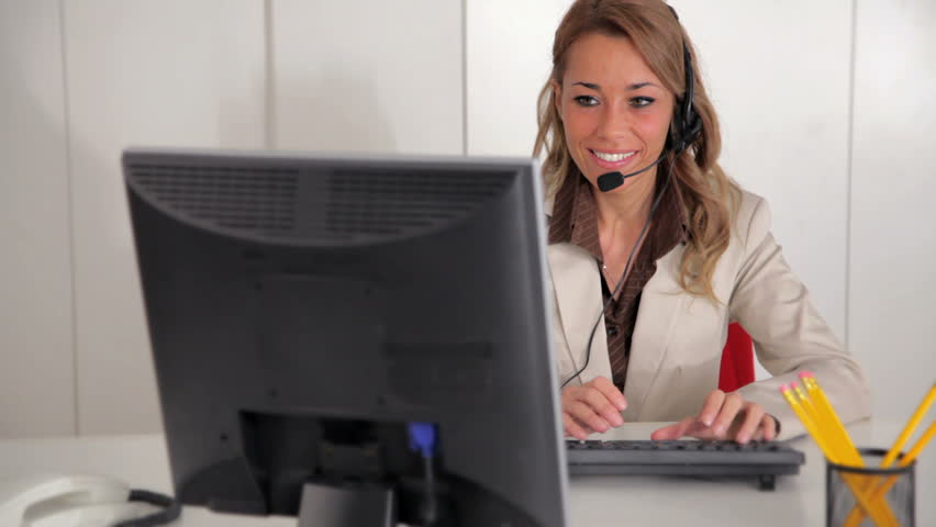 Mid adult female receptionist working on computer and speaking on the phone in office | Shutterstock HD Video #679006
