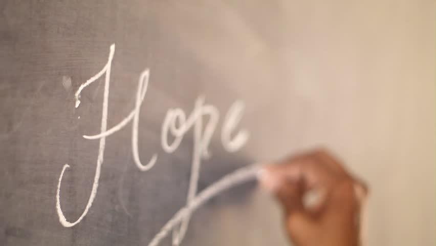 a conceptual video on hope. a guy writing hope on a black board