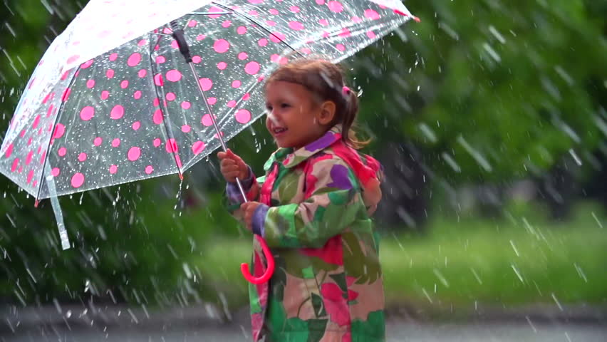 Tilt up of little girl bouncing and splashing happily in the rain