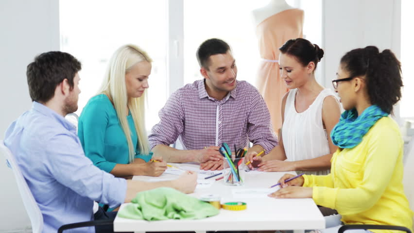 Startup, fashion, teamwork and office concept - smiling fashion designers working in office | Shutterstock HD Video #6833407