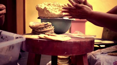 Mexican woman cooking tortillas in a flat griddle