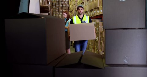Delivery driver loading his van with boxes in a large warehouse
