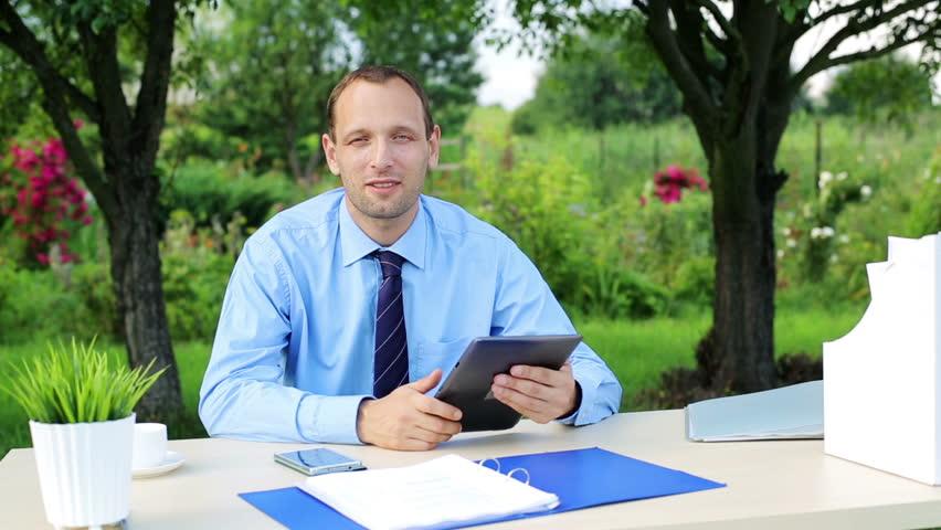 Businessman talking good news to camera, holding tablet  | Shutterstock HD Video #6866338