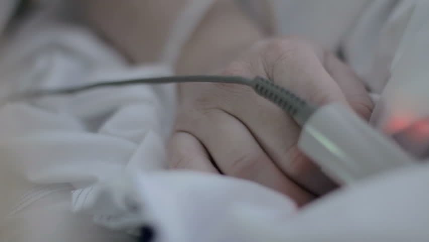 A little girl holds and kisses a hospital patient's hand which has a monitor attached | Shutterstock HD Video #6867760