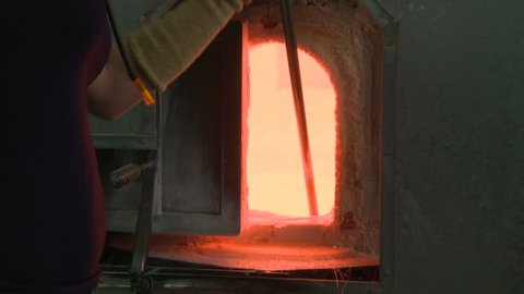 Glassblower pulls hot molten glass from the crucible of a glass furnace