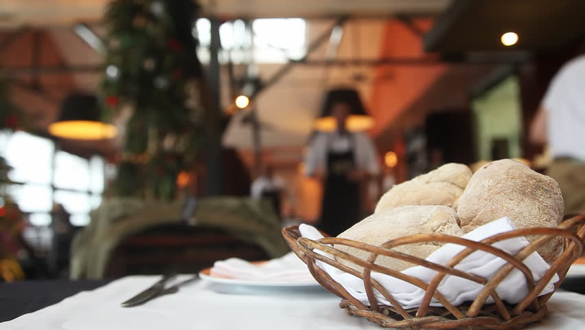 Table setting in restaurant with bread, empty glass and waiters