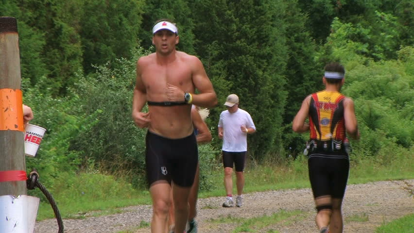 WAYNESVILLE - JULY 5: Runners (names withheld) from Ohio pass at water station during the Caesar Creek Triathlon and Dualthon held at Caesar Creek State Park July 5, 2009 in Waynesville, OH.