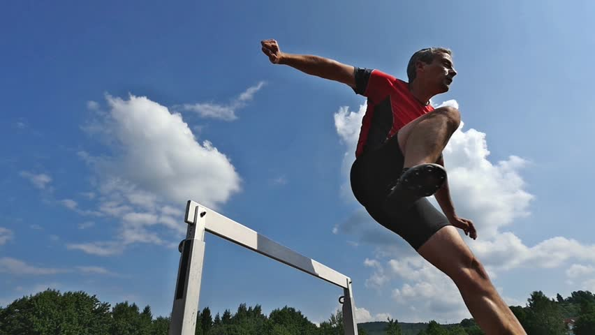 athlete jumping over a hurdle in track and field in slow motion