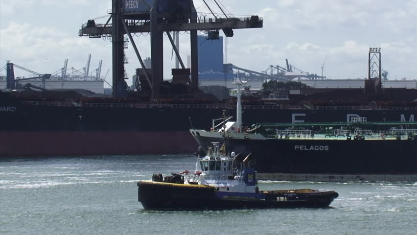 MAASMOND, PORT OF ROTTERDAM - 14 MAY 2014: Crude oil tanker Delta Pelagos inbound  passing EECV terminal + tugboat. Europoort is considered the worlds busiest port and a major entry to Europe.