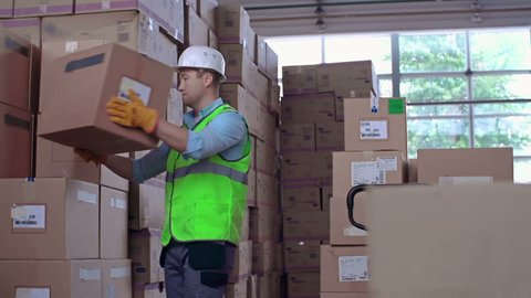 Close up of worker uncarting load and arranging boxes in piles