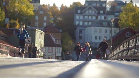 """TRONDHEIM, NORWAY, JANUARY 2014 People crossing the Old City Bridge, """"Gamle Bybro"""" in Trondheim, Norway."""