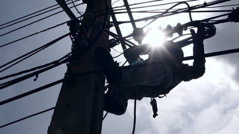 Silhouette of an electrician climbing a newly installed utility pole