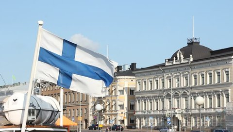 HELSINKI, FINLAND - AUG 2014: Flag of Finland Waving on city background