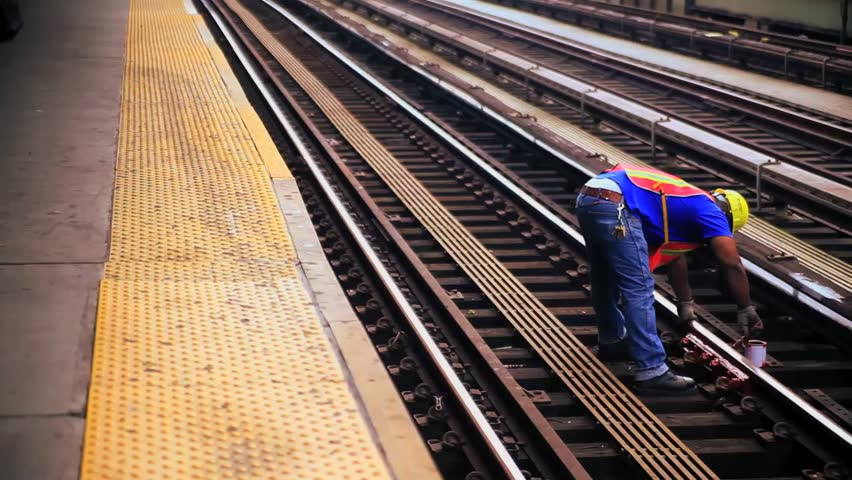 A worker works on the tracks at a train station in New York City. | Shutterstock HD Video #7085458