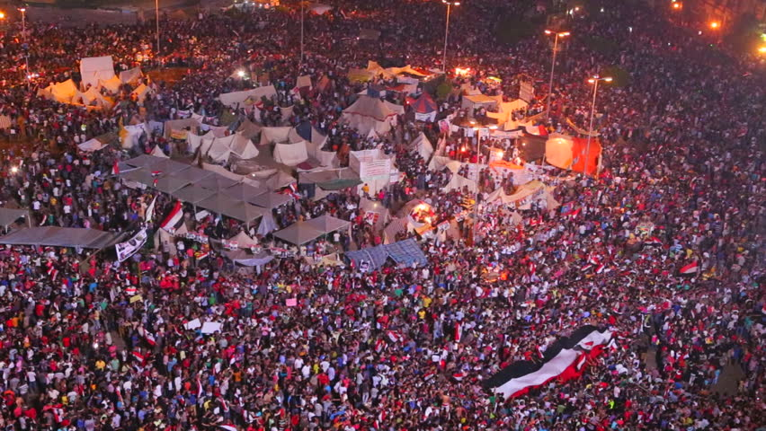 Overhead view as protestors jam Tahrir Square in Cairo, Egypt at a large nighttime rally.