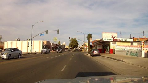 BARSTOW, CA: July 21, 2014- Point of view POV shot of a car driving in downtown circa 2014 in Barstow. A vehicle travels through a small town's business district route off of the major highway.
