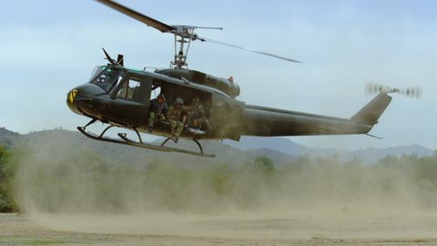 Huey helicopter lands in the desert, slow motion.