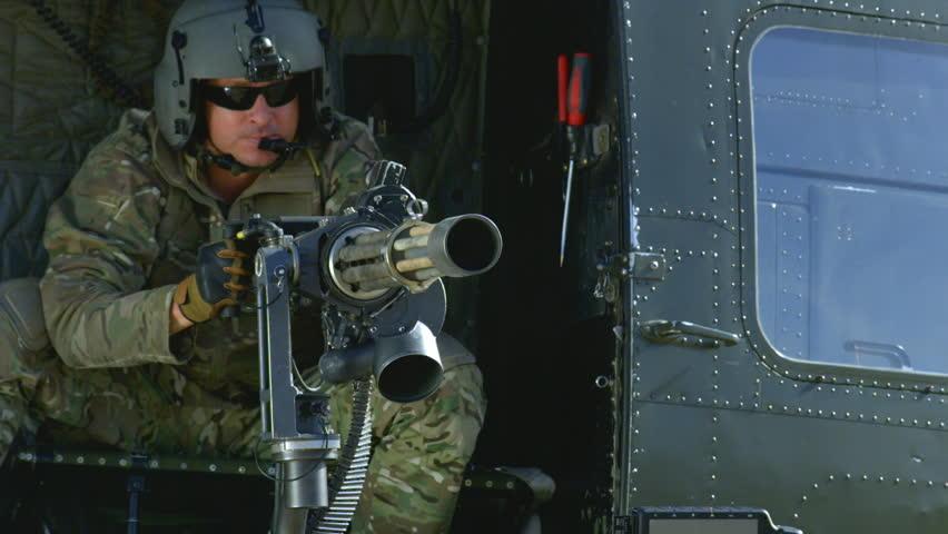 A military man fires the Dillon Minigun in slow motion.