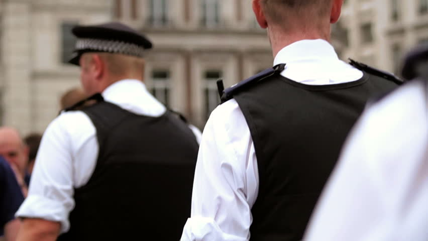 British police officers going through crowd.