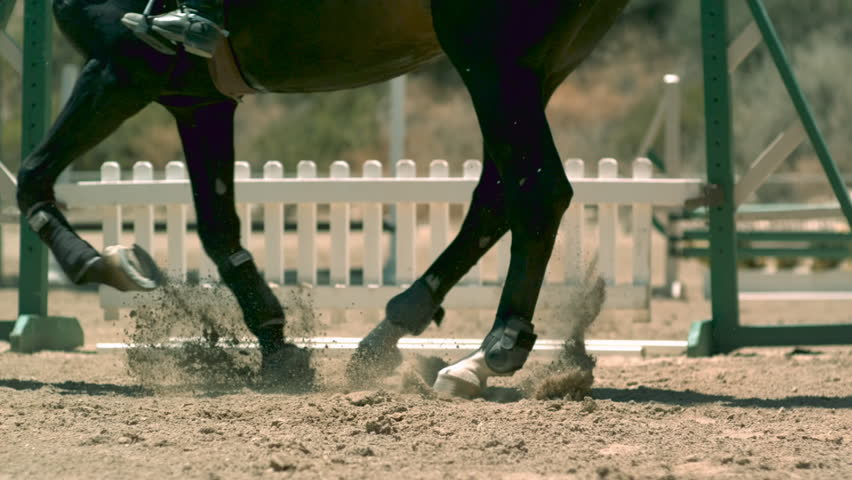 Close up on horse feet, landing in dirt, from a jump.