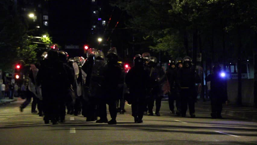 Vancouver, Canada - April 2013 - Group of riot officers marching military step while hitting batons - Commercial license no logo no face