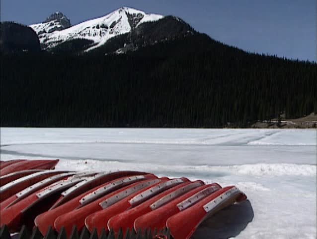 Lake Louise in Rocky Mountains scenery, early spring. Canoes on the bank of  frozen glacial lake + pan Chateau Lake Louise, Banff National Park, Canada.