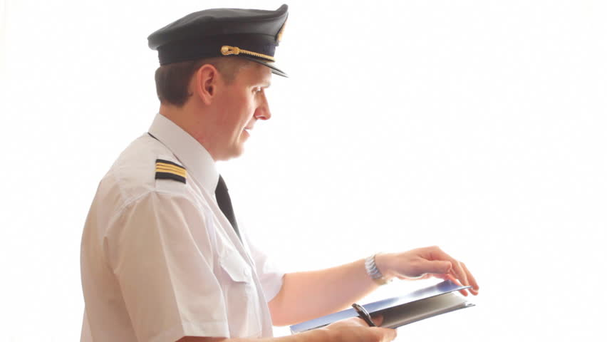 Airline pilot wearing hat, shirt with epaulets and tie filling in and checking papers flight plan, log book and weather forecast.