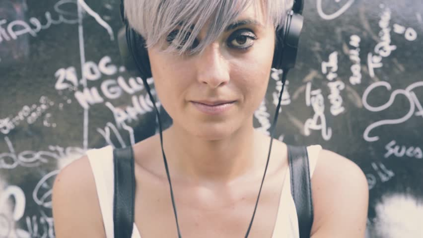young beautiful hipster woman with blue hair listening to music and using smartphone