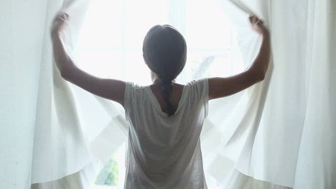 Girl opens the curtains in the morning, slow motion