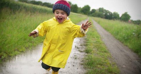 Happy little boy running outside after rain