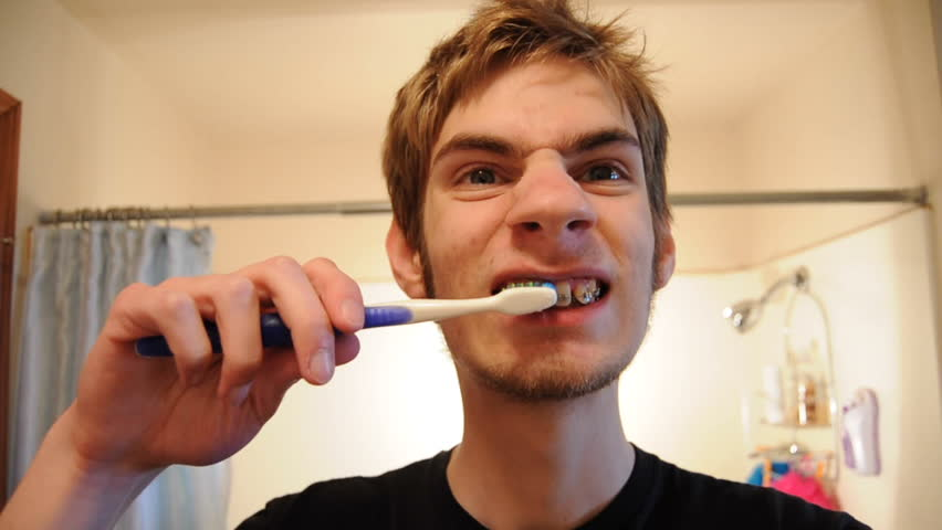 Young adult male brushes his teeth in a bathroom staring into the mirror. He has braces.