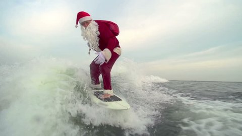 Man in Santa Claus costume with gift bag freestyling on wake surf touching water