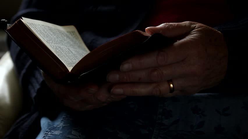 Close up of hands holding a bible
