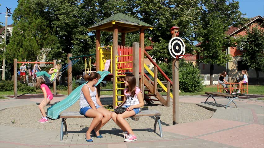 Children Playing In The Park Young Girls Sitting On Bench Swinging A