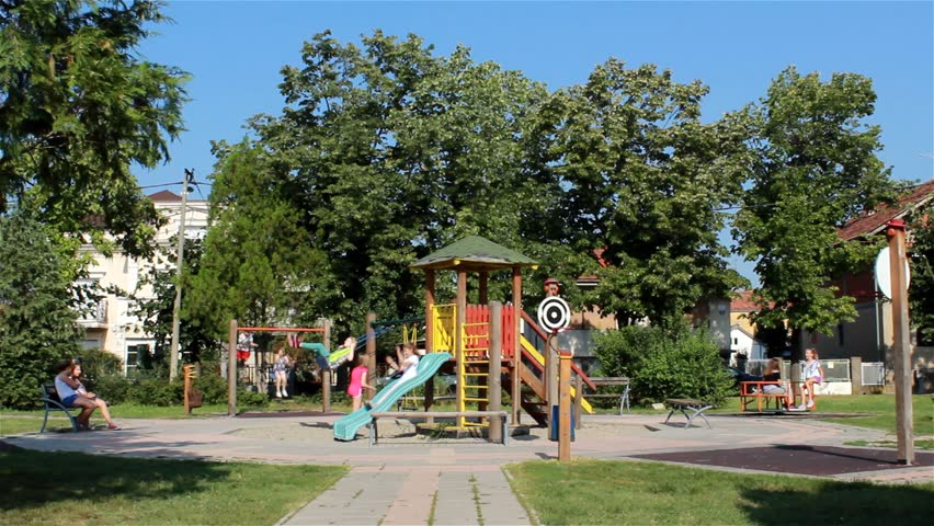 Young Girls Sitting On The Bench Swinging A Swing Going Down Slide Spin Merry Go Round Kids Game Playground Childhood