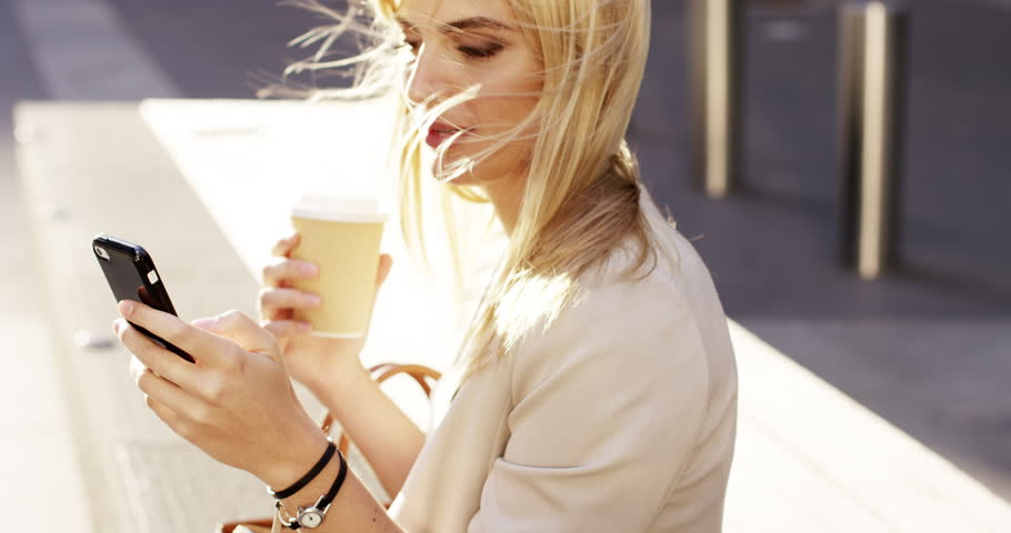 Attractive blonde business woman using smart phone drinking coffee commuter in city london - RED EPIC DRAGON 6K
