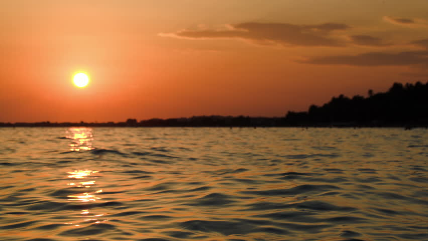 Beautiful Orange Sunset Over Dark Wavy Sea Sun Reflecting In Water