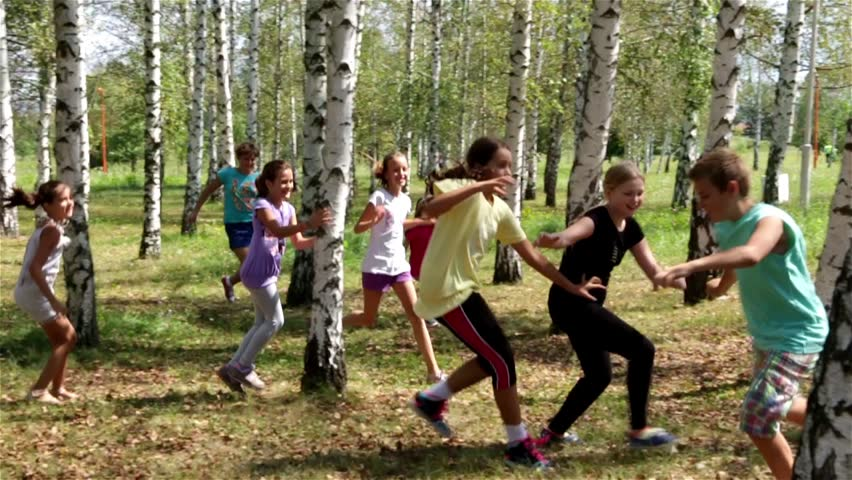 Group of children playing the game with running through the forest. Young girls catching boy around the birch trees. Kids game in the park. Teens playing in the nature. Childhood. Slow motion. 30 fps.