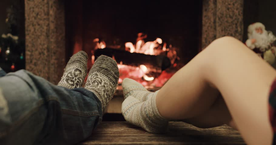 Feet in woolen socks warming by cozy fire in Christmas time in slow motion. Family couple warming their feet by the fireplace in winter time. Filmed at 120 fps 4k graded from RAW