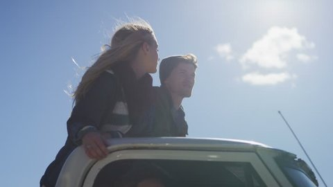 A couple stands in the bed of a pickup truck as it drives along a rural road.